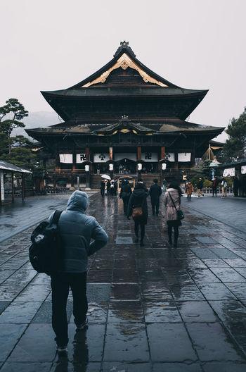 Rear view of people walking on wet street