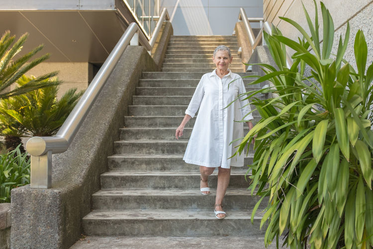 Woman in white dress on stairs with green plant Staircase Full Length One Person Adult Architecture Steps And Staircases Standing Front View Portrait Smiling Looking At Camera Day Plant Women Holding Mature Adult Emotion Clothing Fashion Senior Women