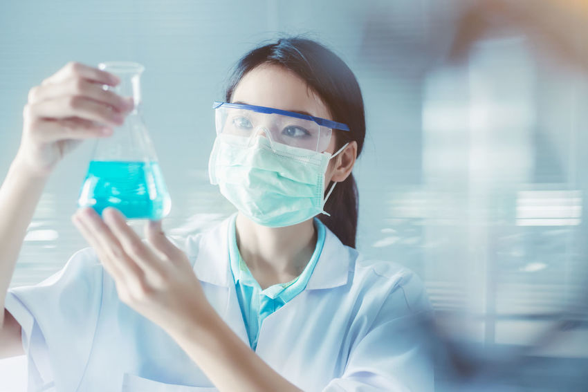 Adult Analyzing Education Front View Headshot Healthcare And Medicine Holding Indoors  Lab Coat Laboratory Laboratory Glassware Occupation One Person Portrait Protection Protective Eyewear Research Safety Science Scientific Experiment Scientist Women