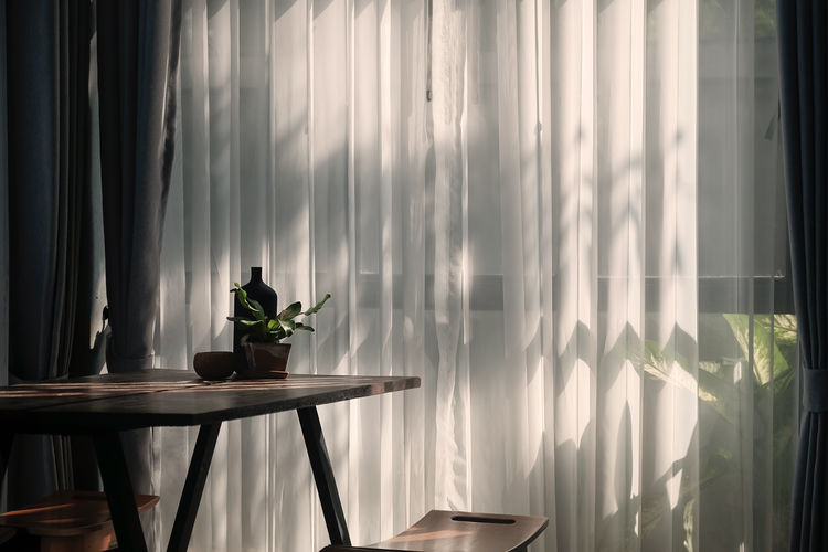 White curtain hanging against window at home