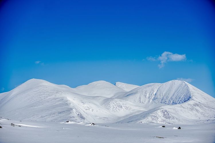 Low angle view of snowcapped landscape against blue sky