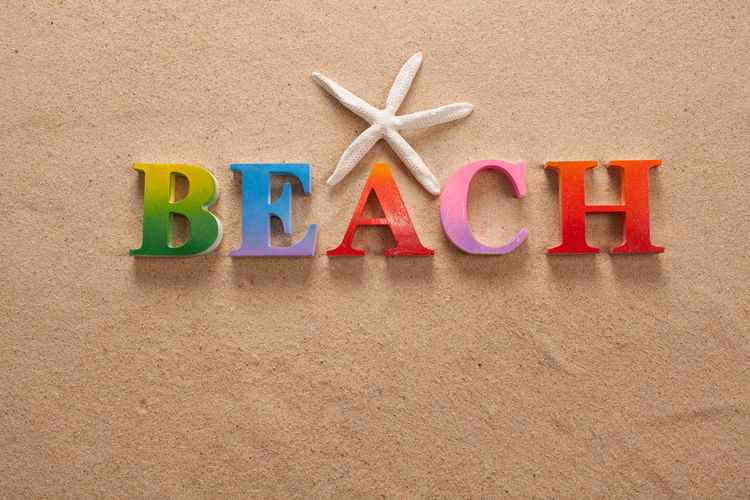 top view of beach written in colorful letters decorate with shellfish on the beach with copy space
