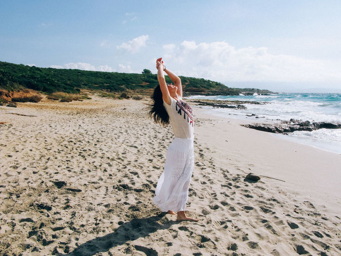 Woman with arms raised standing on sand against sea at beach
