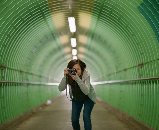 Portrait of young woman photographing with camera while standing in green tunnel