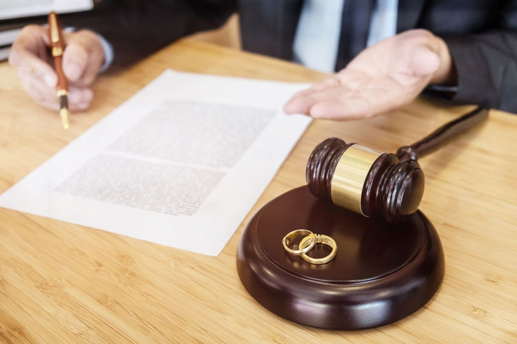 High angle view of rings over gavel by lawyer gesturing by papers on table