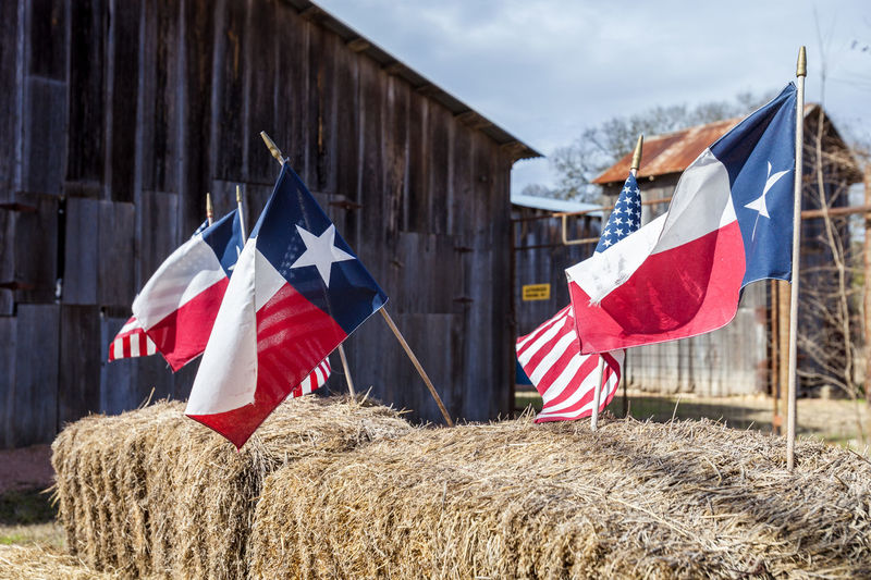 4th of July decoration with the American and Texas flags 4th Of July Cowboy Texas Banner Close-up Countryside Day Flag Flags Independence Day Lone Star State Nature No People Outdoors Patriotism Red, White And Blue Rural Scene Sky Star Stars And Stripes Straw Bales Symbol Wind