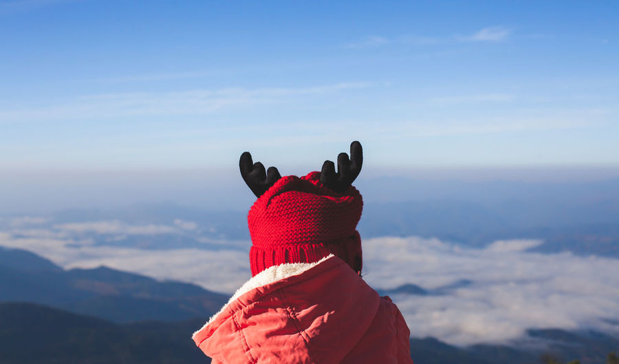 Girl In Warm Clothing Against Blue Sky During Winter