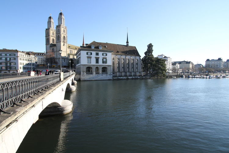 Grossmunster, Wasserkirche and Munsterbrucke - Zurich. Wasserkirche and Helmhaus museum - with Grossmunster to the left - as seen from Stadthausquai and Munsterbrucke. The Wasserkirche (Water Church) was originally built on a small island where, according to legend, the city's martyrs Felix and Regula were executed by the Romans. http://pics.travelnotes.org/ Church Cityscape Travel Travel Photography Zürich Arches Architecture Bridge Bridge - Man Made Structure Building Exterior Churches City Day Grossmünster Münsterbrücke Outdoors Place Of Worship Religion Spirituality Switzerland Tourist Attractions Travel Destinations Travel Pics Wasserkirche Water