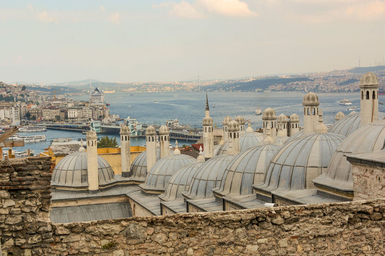 High angle view of domes and buildings by strait against sky