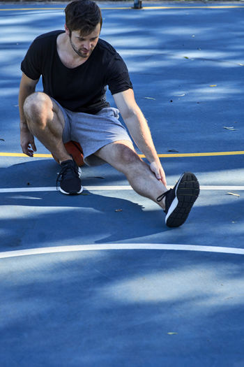 Full Length Of Young Man Stretching Leg While Exercising On Road