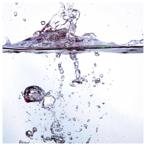 Close-up of water splashing against white background