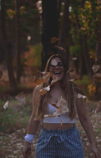 Cheerful woman with mouth open throwing leaves in forest