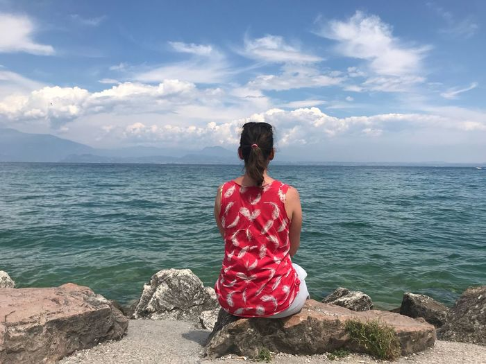 Rear view of woman sitting on rock at beach against sky