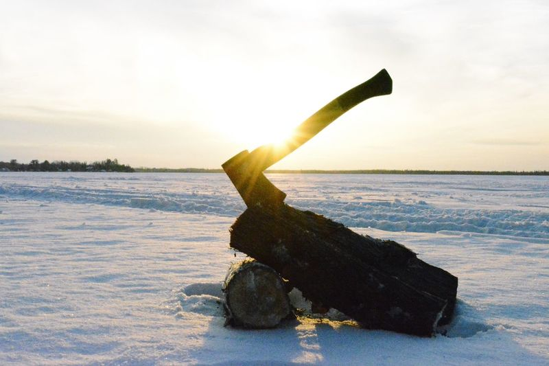 Close-up of axe and wood on snow covered field against sky during sunset
