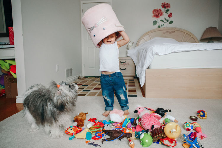 Funny baby toddler girl with toy bin on head. kid child playing with toys at home.