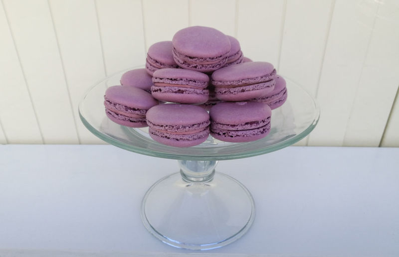 Pink Macaroons Stacked On Cake Stand On Table Against Wood Paneling
