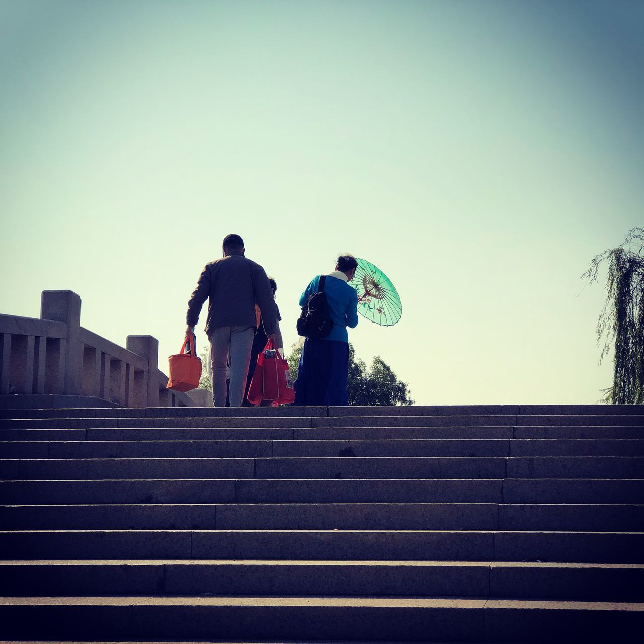 REAR VIEW OF PEOPLE ON STAIRCASE AGAINST SKY