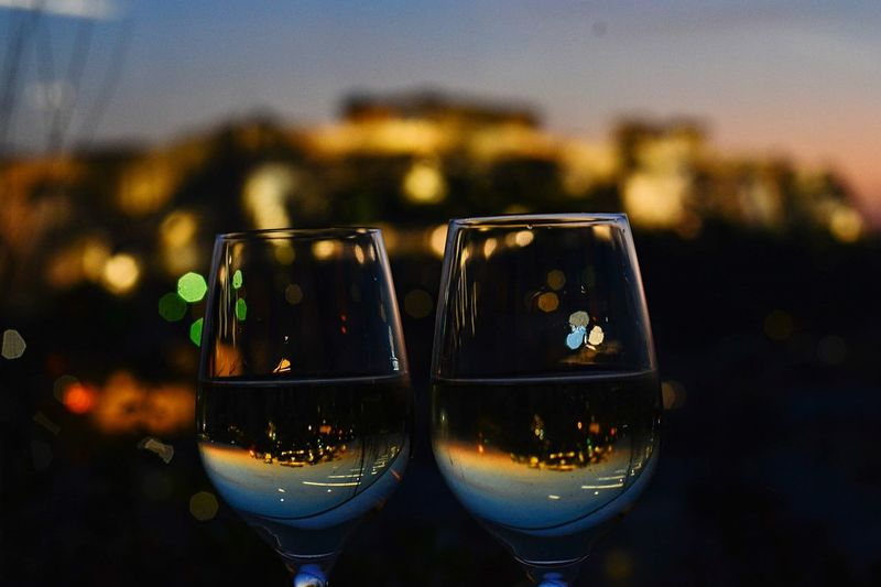 Acropolis reflections Evening High Angle View Landscape Reflection Wineglass Glass Alcohol Drink Refreshment Focus On Foreground Close-up Food And Drink Wine Glass - Material Household Equipment No People Drinking Glass Sky Nature Champagne Celebratory Toast Still Life Table Sunset