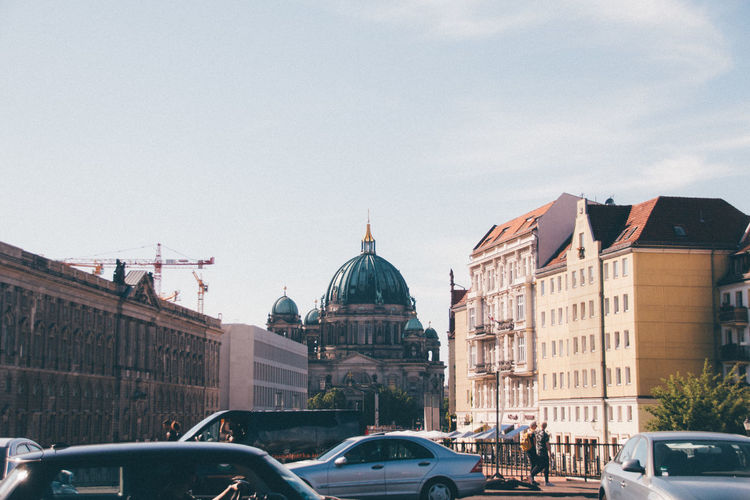 Berlin cathedral by buildings against sky