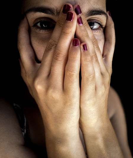 Close-up portrait of woman covering face with hands