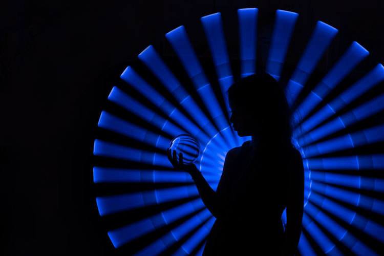 Silhouette girl standing against illuminated lighting equipment