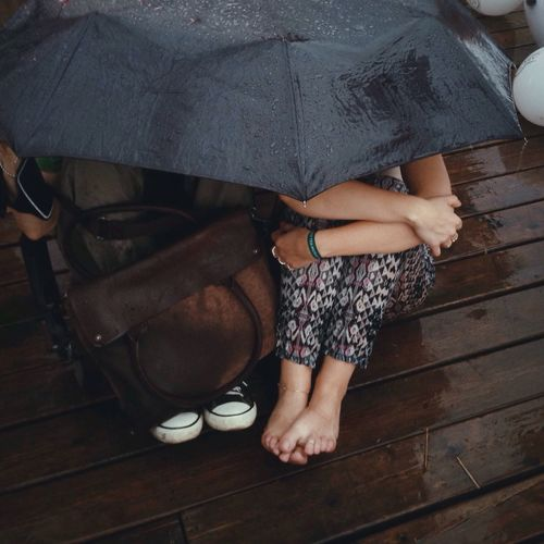 High angle view of couple sitting under umbrella on wet pier in rain