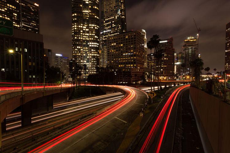 Light trails on bridge by illuminated buildings at night
