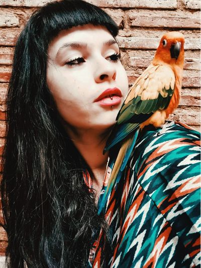 Close-up portrait of young woman with her parrot