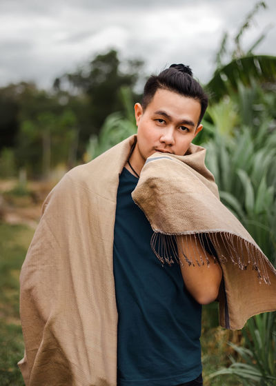 Portrait of young man with scarf standing against plants