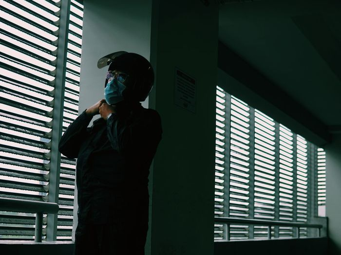 Low angle view of man wearing flu mask standing against window