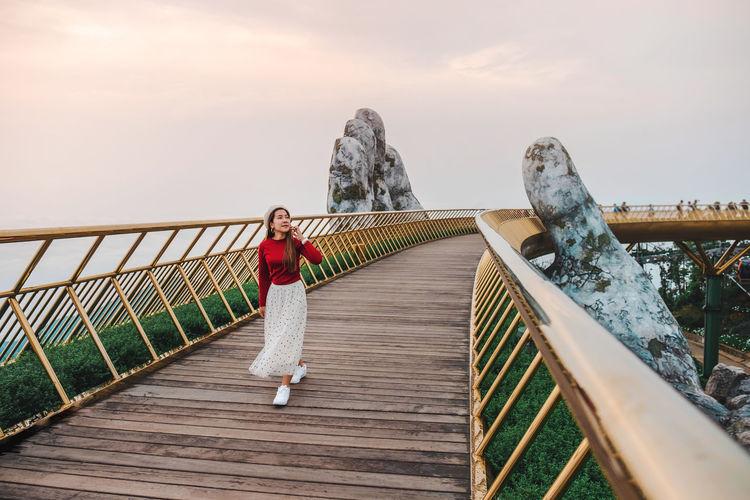 Full length of woman standing on footbridge against sky