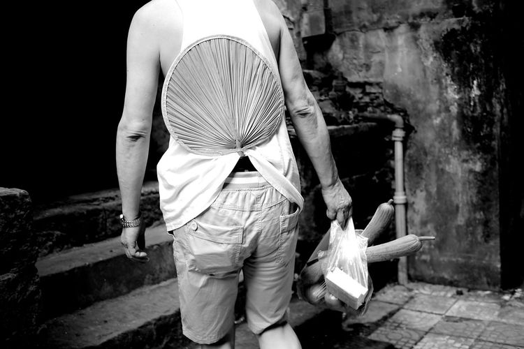 Rear view of man with hand fan inserted in pants carrying grocery bag