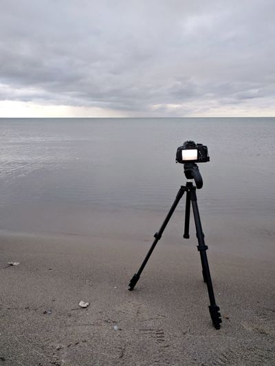Close-up of camera on beach against sky