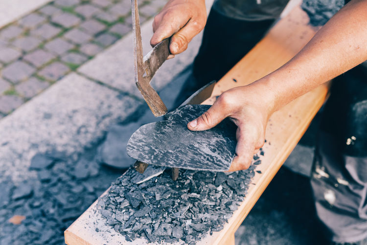 a roofer makes a heart of slate Roofer Close-up Craftman Craftmanship Day Hand Tool Heart Shape Holding Human Body Part Human Hand Men One Person Outdoors People Real People Slate Work Tool Working