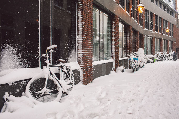 Bicycle on snow covered street by buildings in city