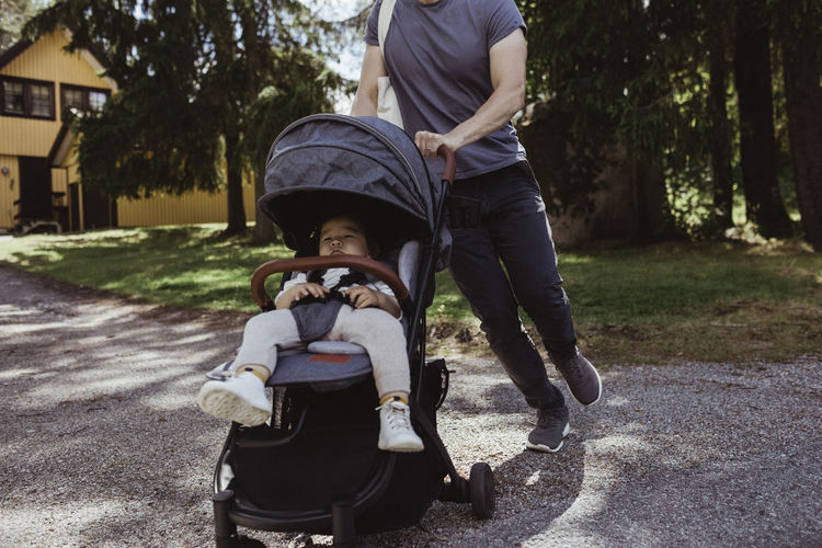 Rear view of father and son on footpath