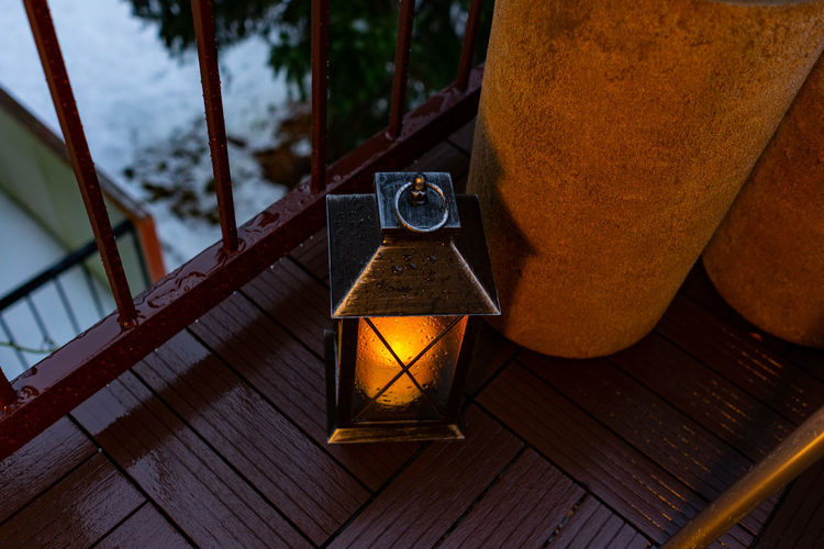 A candle on the balcony No People Lighting Equipment Focus On Foreground Close-up Wood - Material Illuminated Indoors  Architecture Lantern Wood Table Day Electric Lamp Built Structure Railing High Angle View Glass - Material Nature Glass Balcony
