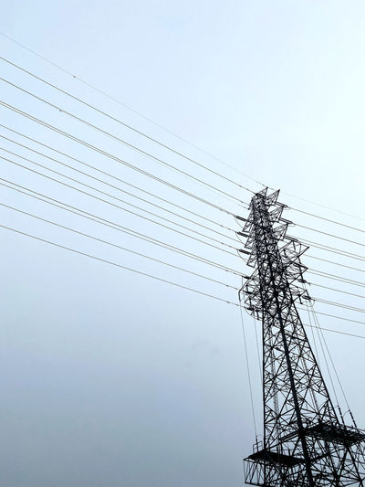 Low angle view of silhouette electricity pylon against clear sky