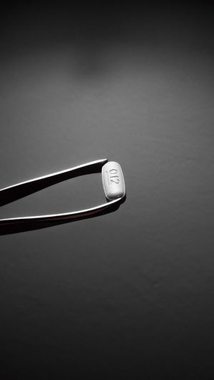 Tweezers Holding A Pill Over Gray Background