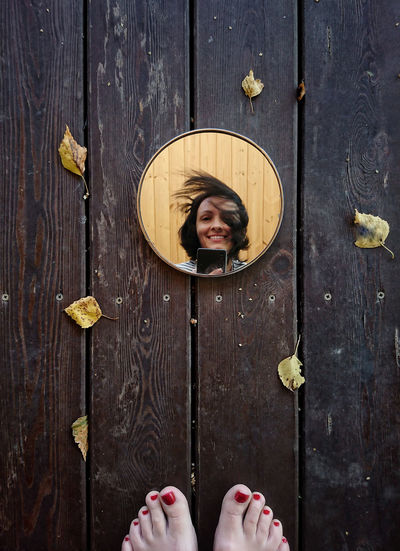 Portrait of smiling woman standing against door