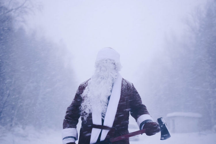 Mid Adult Man In Santa Costume Standing In Forest During Winter