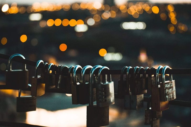 Close-Up Of Padlocks Hanging On Railing At Dusk