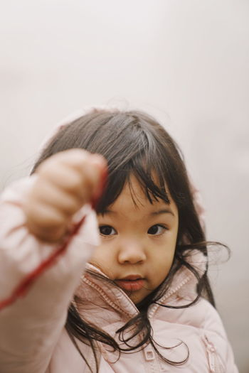 Close-up portrait of cute girl standing outdoors during foggy weather