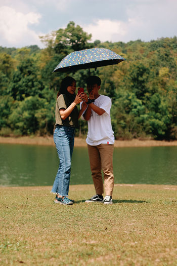Rear view of couple standing by lake