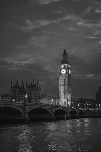 Westminster bridge over river against sky in city