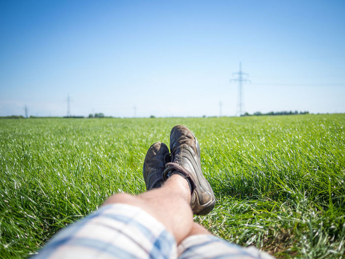 Low section of man lying on field against clear sky