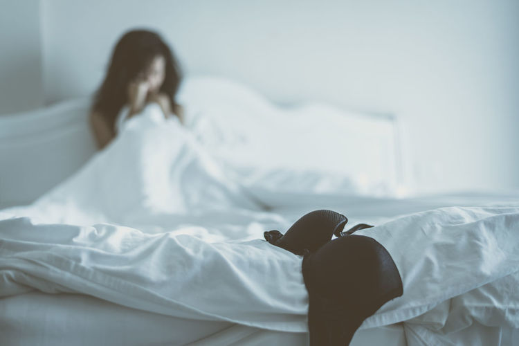 Terrified Woman Sitting On Bed With Bra In Foreground