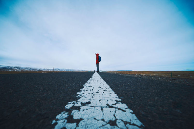 Side view of man standing on road against sky