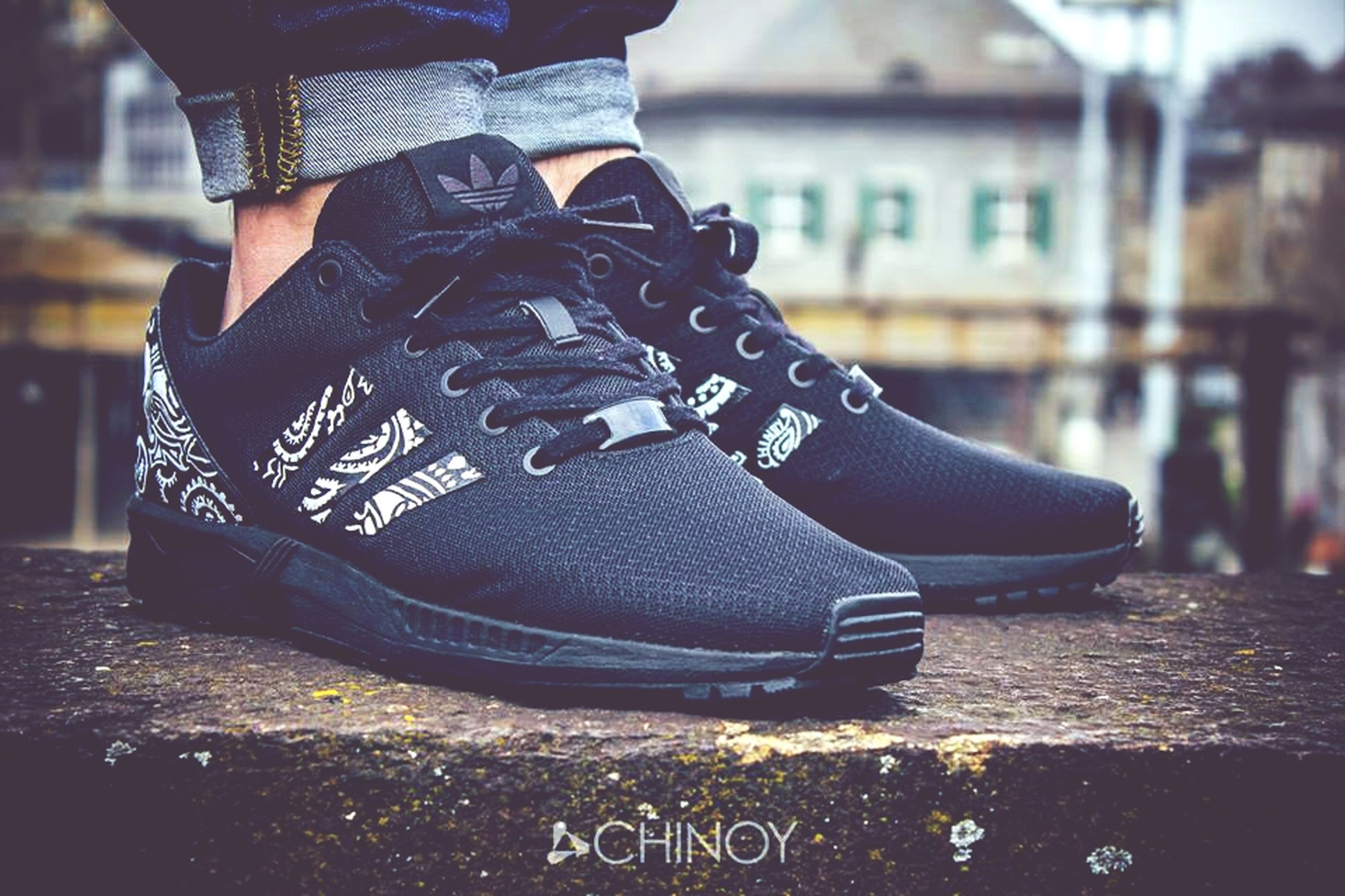 focus on foreground, lifestyles, text, low section, leisure activity, standing, men, western script, communication, street, person, close-up, casual clothing, midsection, shoe, selective focus, holding