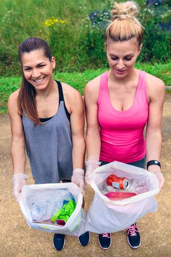 Female Volunteers Showing Garbage In Plastic Bags